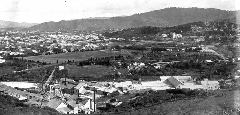 View from Union Hill overlooking the Waihi Battery, and much of the ground now traversed by Mill Stream Walkway. Middle left is the Recreation ground (now known as Morgan Reserve) with Baker Street on its left hand edge. The water race pipe taking the water captured from Mill Stream to the battery is visible, the original tennis courts and shelter are nearer the centre of the picture. The Battery managers house is clear at centre, and to the right of that the driveway into the quarry. The large building at middle right is the New Central Hotel, on the corner of Kenny Street and Barry Road, where the children's' playground is now. Martha Hill with Cornish Pumphouse top right. Photo c.1906, ATL 19313.