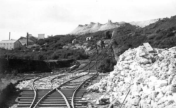 "Incline on Union Hill, showing the portal of the tunnel which took ore from the New Shaft. What was the gauge, 3'6""? Note the lower tailings bund at left of picture, the pile of rubble for ballasting the line, and the small dwellings at top centre. Picture taken from near the ""gorge"" on the walkway"